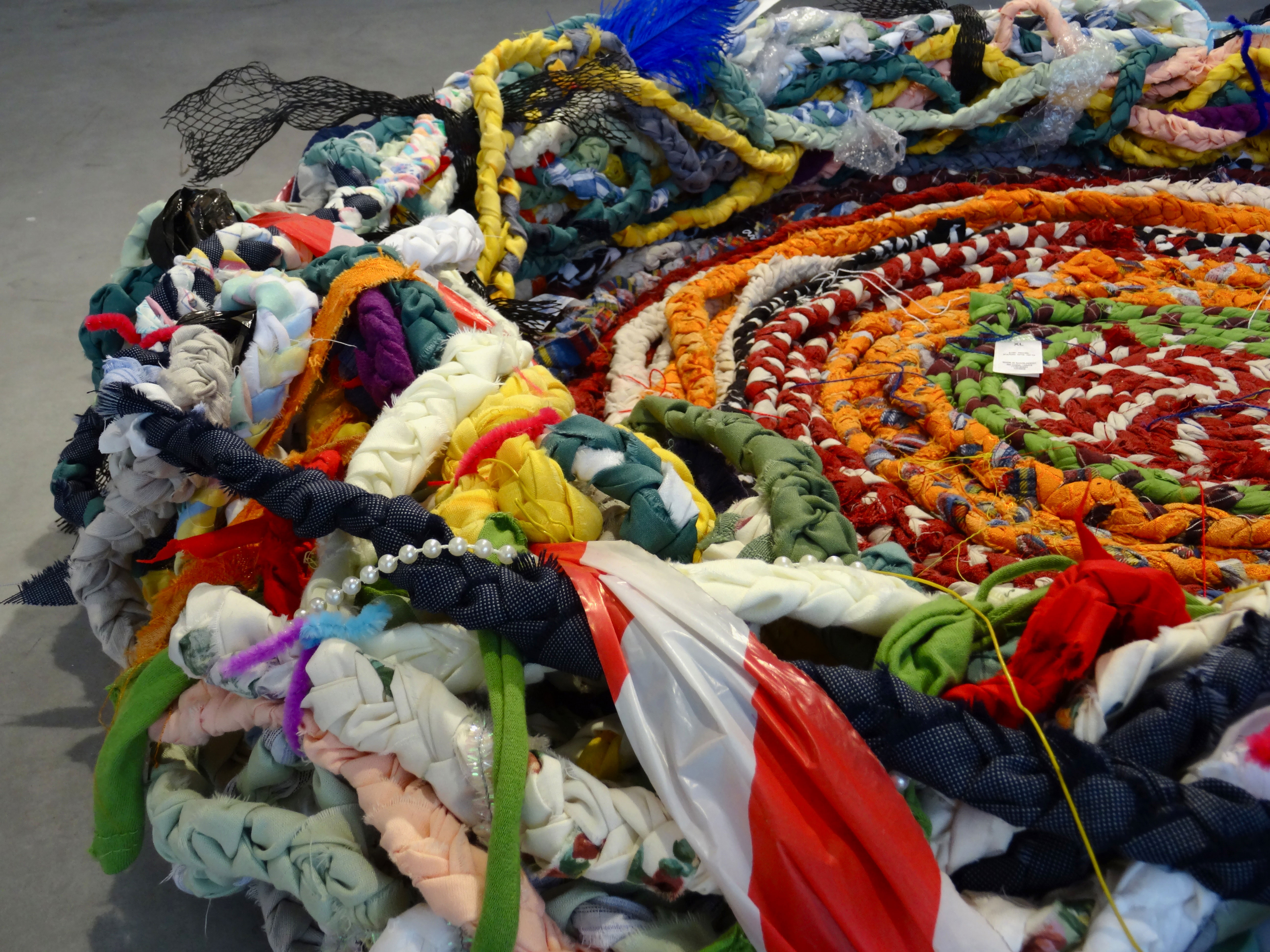 The work resembles a large nest big enough for a human being to sit in. It is made from braided fabric that is spiralled around and there are a variety of materials woven between its layers including feathers, plastic packaging, discarded clothing and costume jewellery. It is brightly coloured from all of the different fabrics used to create the structure. The photograph shows Nest in an exhibition space on a grey floor.