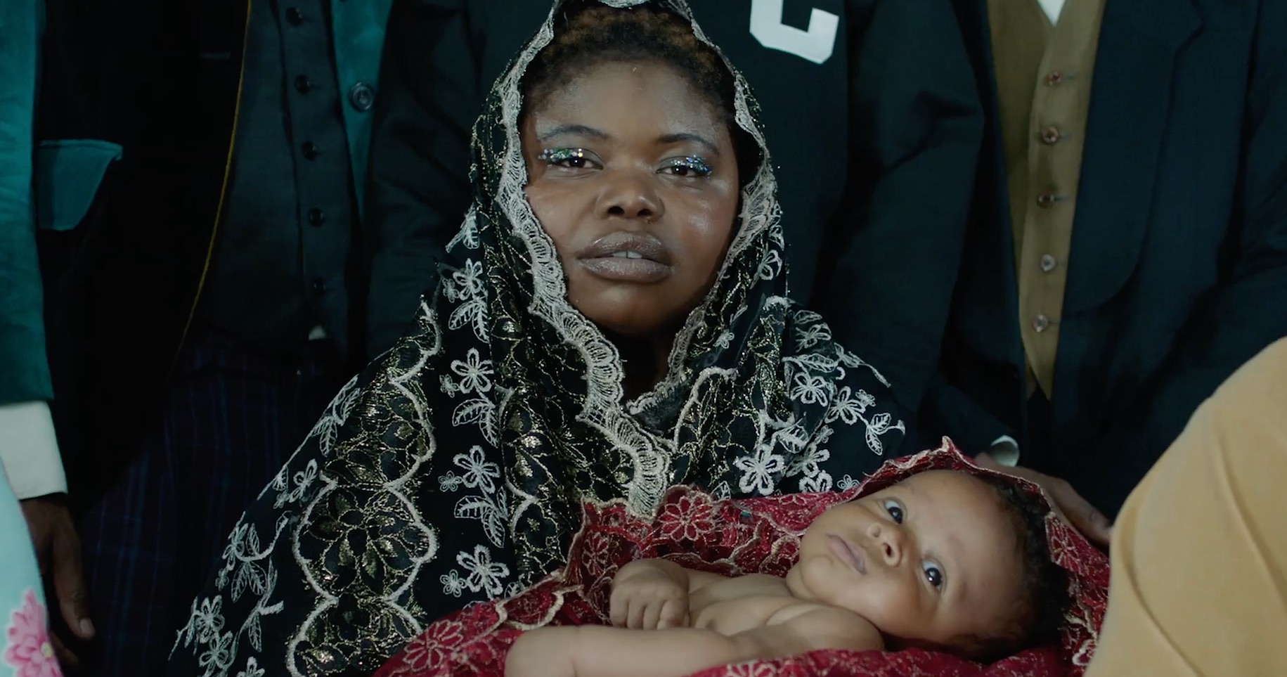 The still image shows a Black individual with a black and white veil, covered in floral motives, which covered the head. The individual holds a baby in their lap. The baby is watching the camera with curious eyes and is covered in a red scarf.