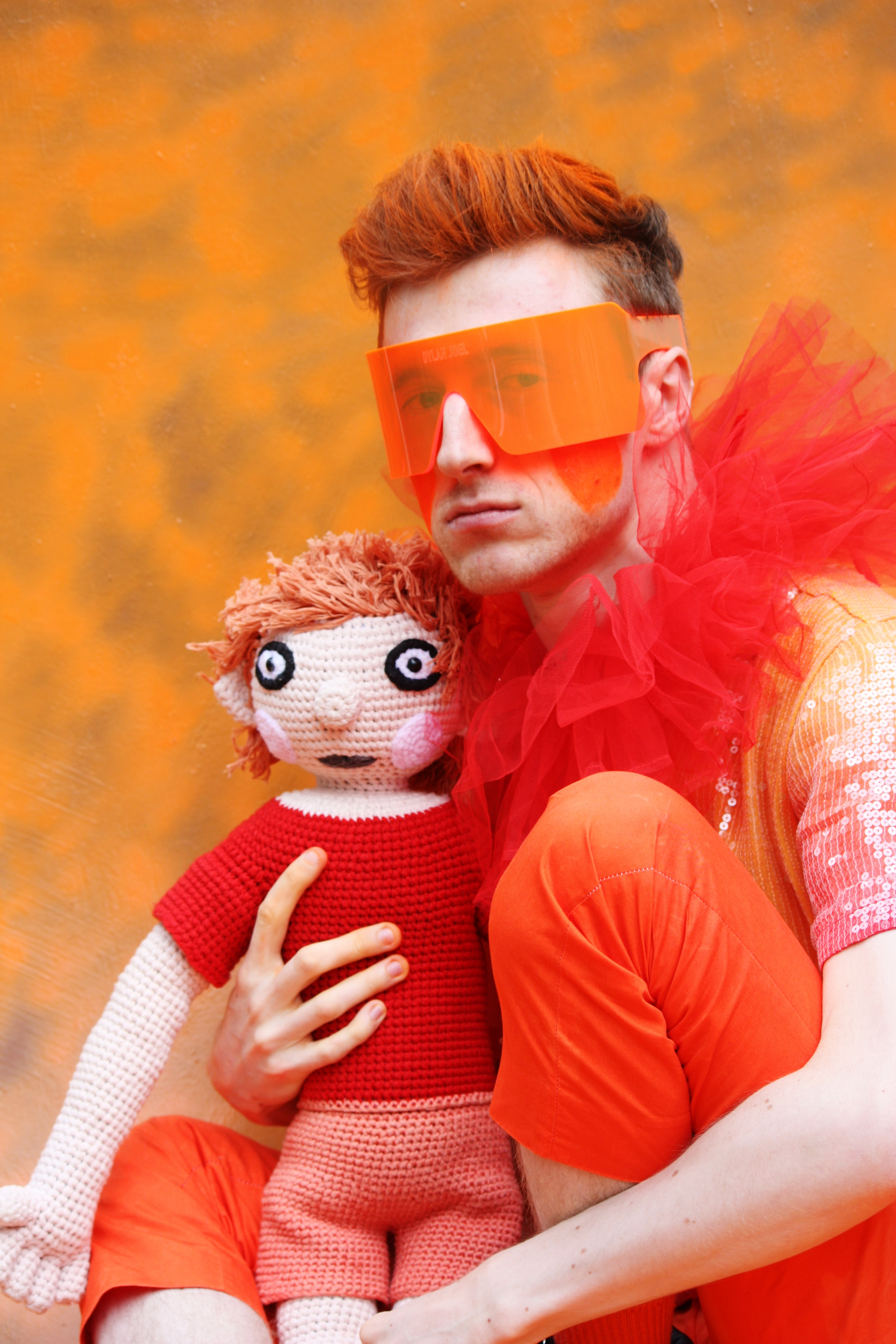 ID: [George is a white, autistic individual with short orange hair dressed in orange clothes, of various textures, sequins, velour, wool, whilst clutching a doll in an affectionate embrace and wearing an orange visor. This image mimics the way a gibbon clutches their baby]