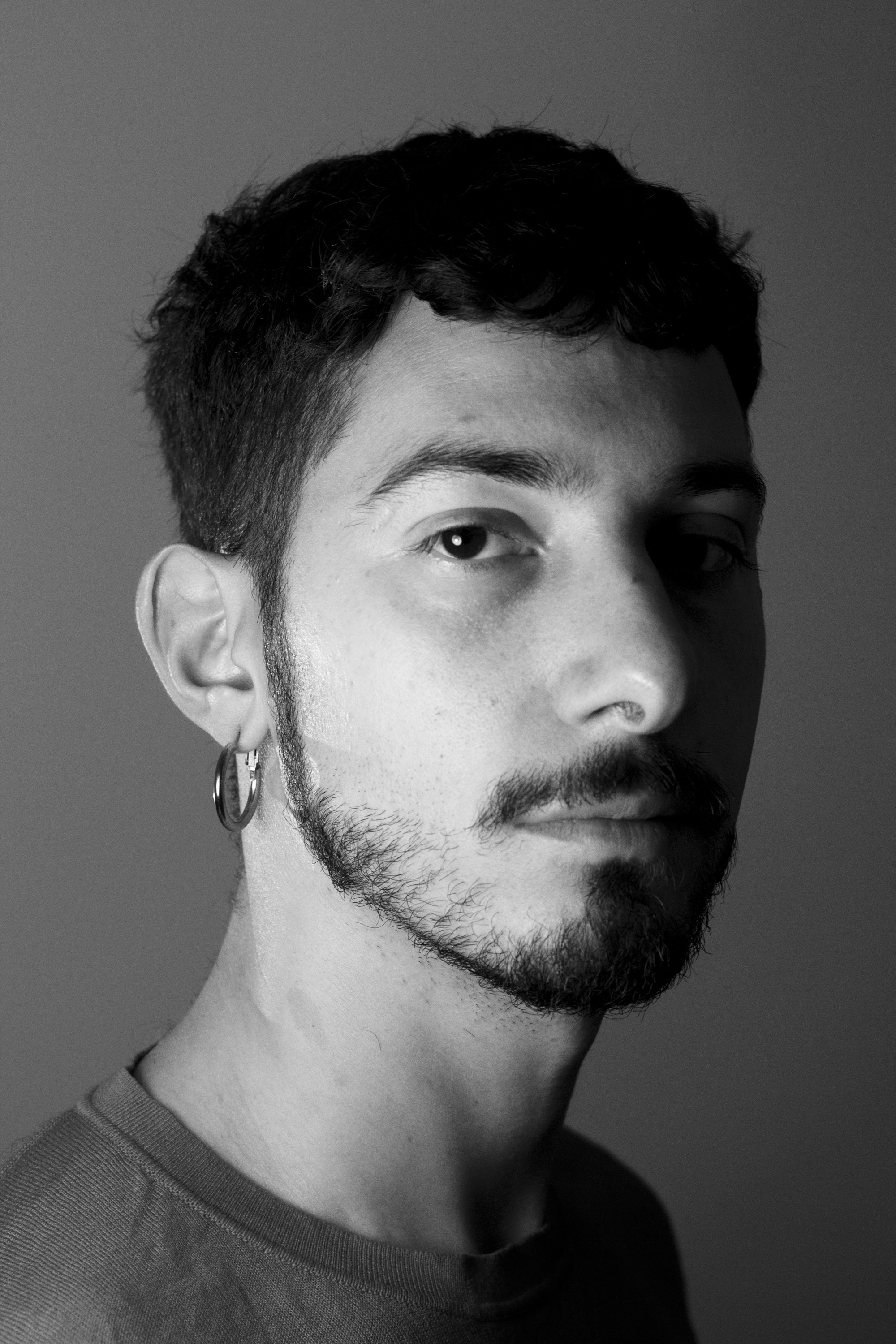 The black and white photo shows Celin an individual with short brown hair and beard, wearing a circle earring