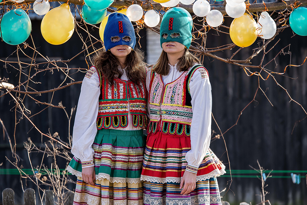 The photo shows two white individuals with long brown hair. The one on the left wears a blue balaclava, the one on the right a water green one. They wear brightly coloured traditional folk dresses, consisting in a knitted top, pleated skirts. On the background coloured balloons and tree branches.
