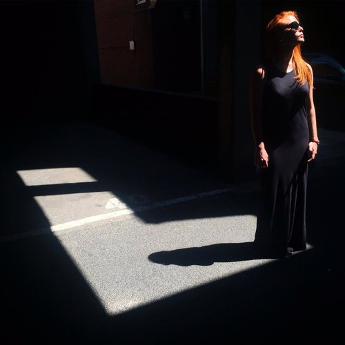 The photo shows Camilla a white individual with long red hair by a window wearing a black dress and black sunglasses. The room where she is is dimly lit