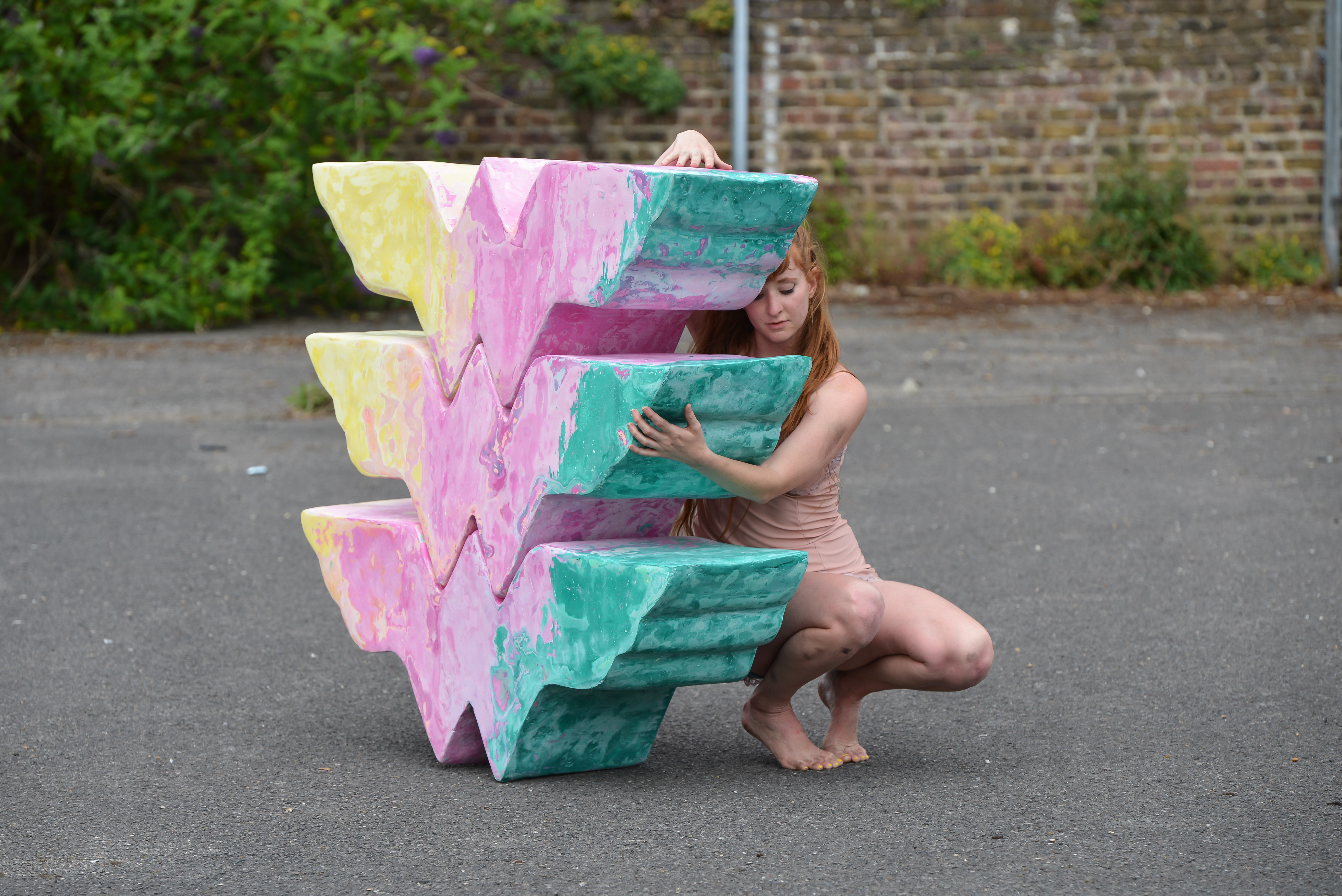 The photo shows Emma, a white individual with long red hair, who stands naked near Candida William's sculptural piece called nothing is harder to understand (strength). The sculpture is yellow, pink and blue and reminds of a totem.